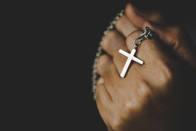 Spiritualità e religione, donne in concetti religiosi mani che pregano dio mentre si tiene il simbolo della croce. nun prese la croce in mano.