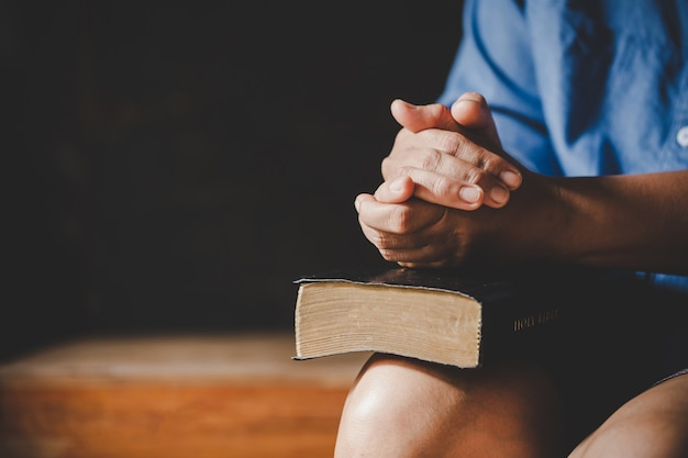 Spiritualità e religione, mani giunte in preghiera su una sacra bibbia nel concetto di chiesa per la fede.