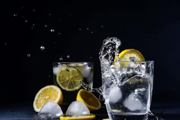 Splash gin and tonic cocktail con fettine di limone il cubetto di ghiaccio cade in acqua con il limone copia spazio, limonata