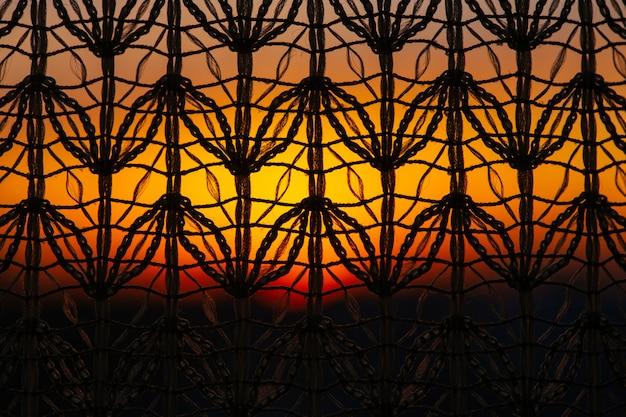 Splendida alba vivida dalla finestra attraverso la tenda a motivi geometrici. incredibile cielo caldo dietro sagome di tulle trama. luce solare arancione. cosiness ha strutturato la priorità bassa variopinta con l'alba. copia spazio.