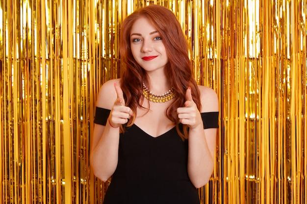 Splendida bella ragazza con i capelli rossi e indossa un abito nero e una collana isolato su orpelli dorati sullo spazio, mostrando i pollici in su