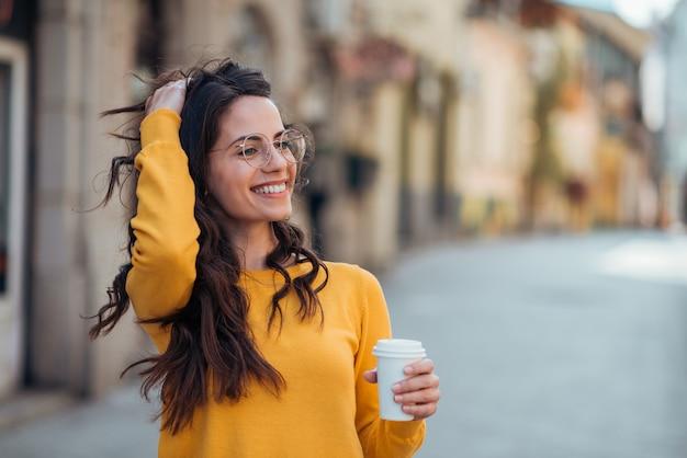 Splendida bruna casual in strada della città, sorridente e bevendo caffè per andare.
