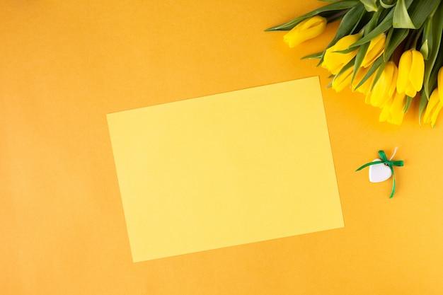 Splendida composizione floreale. tulipani gialli dei fiori, blocco per grafici vuoto per testo su una priorità bassa gialla. nozze. compleanno san valentino. festa della mamma. vista piana, vista dall'alto, copia spazio