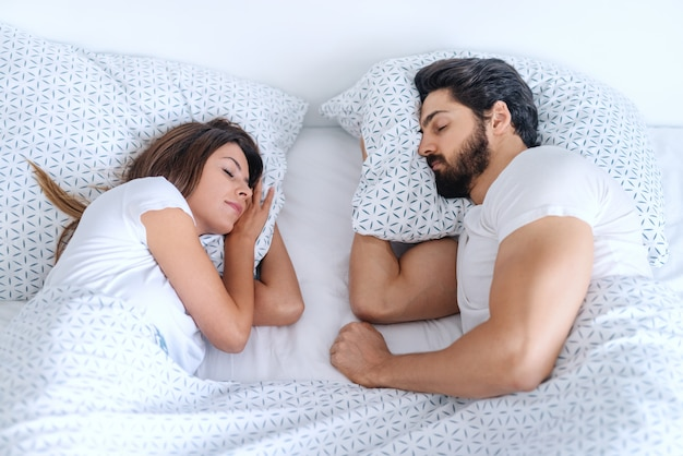 Splendida coppia sdraiata a letto e dormire bene. mattinata.