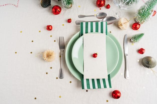 Splendida cornice da tavola su fondo grigio con piatti bianchi, posate e decorazioni natalizie