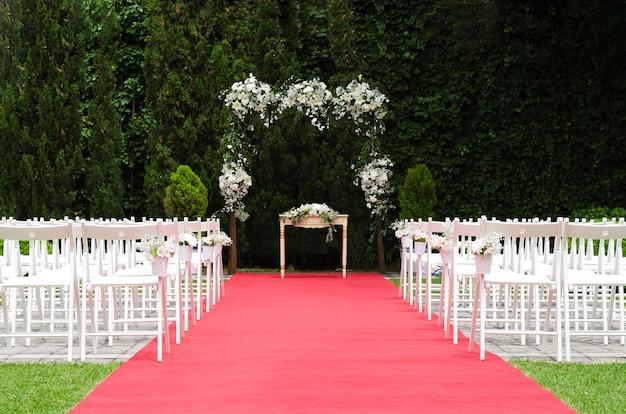 Splendida decorazione per cerimonia nuziale, altare rustico decorato con fiori di gigli, alstroemerie e crisantemi dietro il muro di edera, tappeto rosso con sedie bianche. concetto di giorno del matrimonio.