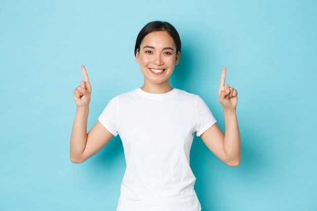 Splendida donna asiatica sorridente giovane 20s in abiti casual, puntando il dito verso l'alto, mostrando pubblicità, dimostrando offerta promozionale. ragazza coreana che indica a, parete blu