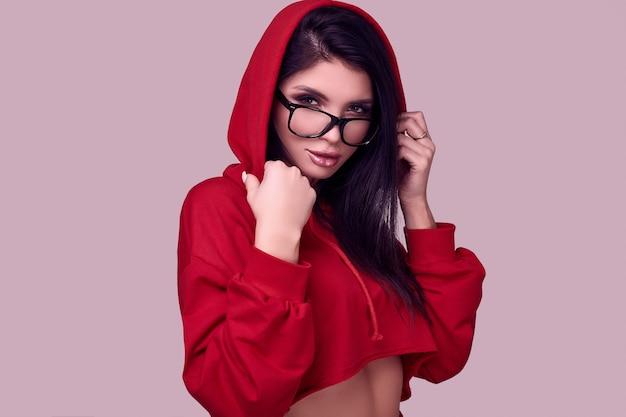 Splendida donna bruna in felpa con cappuccio rosso moda