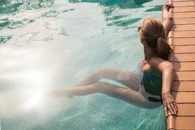 Splendida donna naturale bella in piscina sorridente felice.
