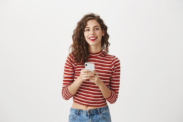 Splendida donna utilizzando il telefono cellulare e sorridente