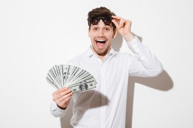 Splendida foto di uomo eccitato in camicia togliendosi gli occhiali da sole neri e godendo il fan delle banconote da un dollaro con piacere e gioia, isolato sopra il muro bianco con ombra
