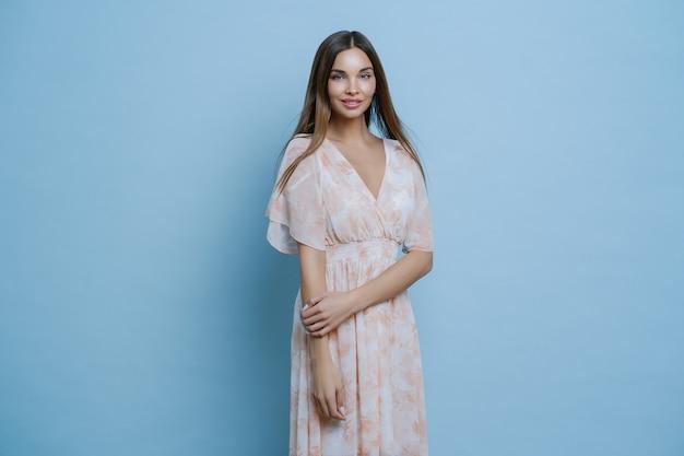 Splendida giovane donna attraente in lungo abito di seta, pronta per uscire per una romantica data estiva, ha un'espressione affascinante, ha un aspetto elegante.