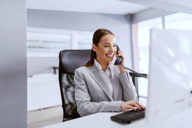 Splendida imprenditrice caucasica con lunghi capelli castani e in abbigliamento formale utilizzando il computer
