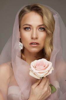 Splendida modella bionda in velo rosa. trucco naturale che indossa un velo rosa e che tiene una fragile rosa rosa.