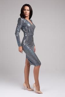 Splendida modella in abito da cocktail e tacchi argento scintillanti.