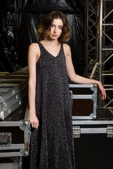 Splendida modella in posa nel backstage in abito lungo con paillettes