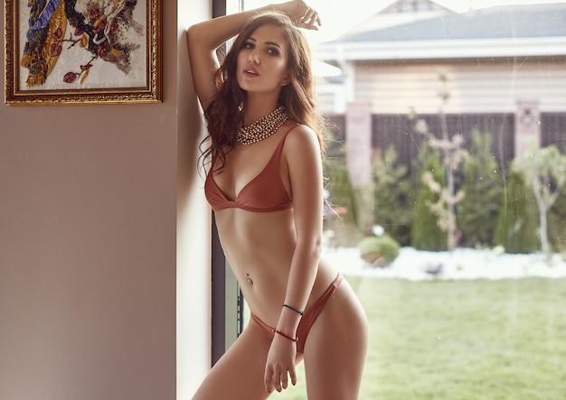 Splendida modella sensuale in costume da bagno moda in posa vicino alla finestra