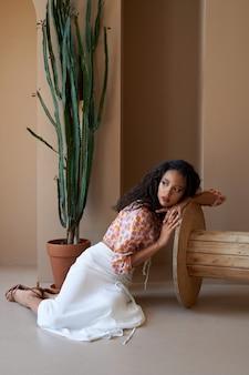 Splendida ragazza mulatta con i capelli ricci in posa vicino alla pianta succulenta alta in vaso di fiori, seduta sul pavimento e appoggiata su una ruota di legno