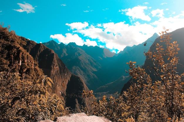 Splendida ripresa di una catena montuosa piena di alberi e un cielo blu nuvoloso in una giornata fredda