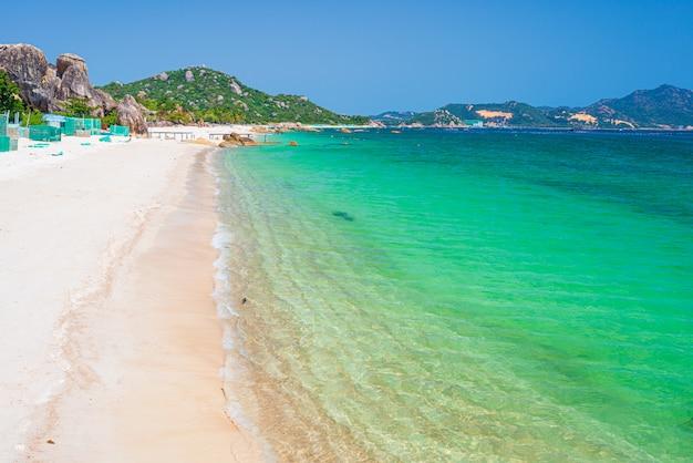 Splendida spiaggia tropicale turchese trasparente acqua massi di roccia unici, cam ranh nha trang vietnam costa sud-est destinazione di viaggio, spiaggia cielo blu chiaro