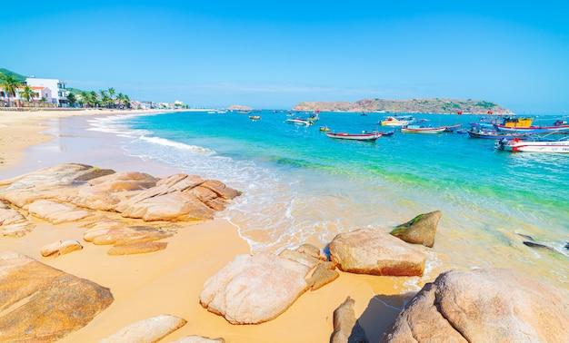 Splendida spiaggia tropicale turchese trasparente acqua massi rocciosi unici, barca da pesca e villaggio nhon hai, quy nhon vietnam costa centrale destinazione di viaggio, spiaggia di sabbia