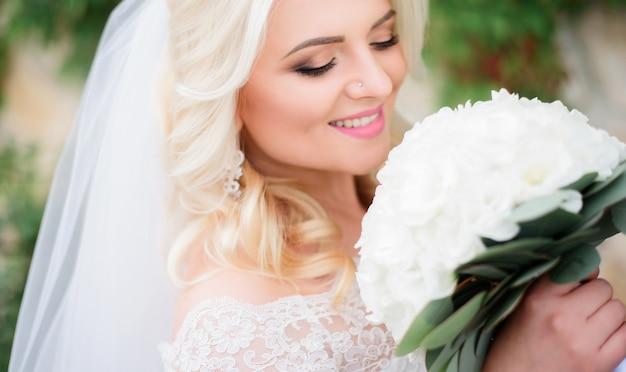 Splendida sposa bionda con bouquet bianco si trova sul cortile