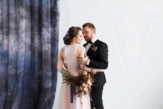 Splendida sposa in un tenero abito da sposa e lo sposo elegante e virile abbraccia la futura moglie
