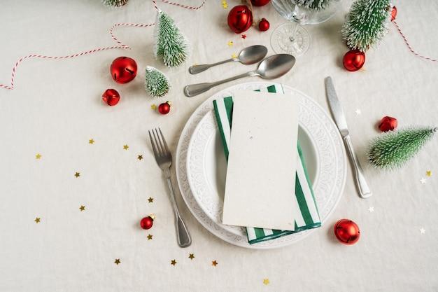 Splendida tavola di natale con spazio per menu o invito su piatti bianchi con posate d'argento