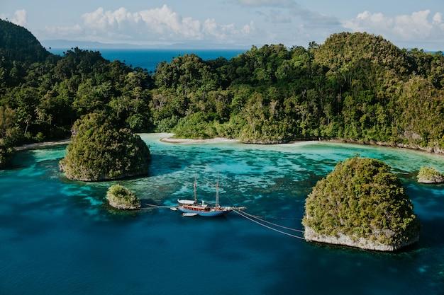 Splendida vista sul mare di raja ampat papua con barca nel mezzo