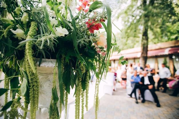 Splendida zona fotografica per matrimoni nel parco all'ombra, uno schermo bianco, un piedistallo con fiori e decorazioni.