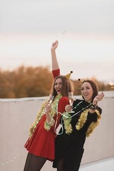 Splendide donne che si divertono sulla festa sul tetto