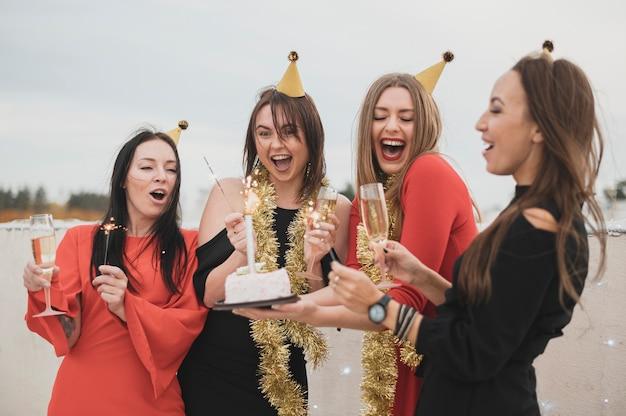 Splendide ragazze che tengono la torta di compleanno su una festa sul tetto