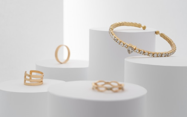 Splendido bracciale prezioso con collezione di diamanti e anelli su piattaforme bianche.
