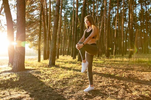 Splendido corridore femminile facendo esercizio di stretching, allenamento nel bosco al sole