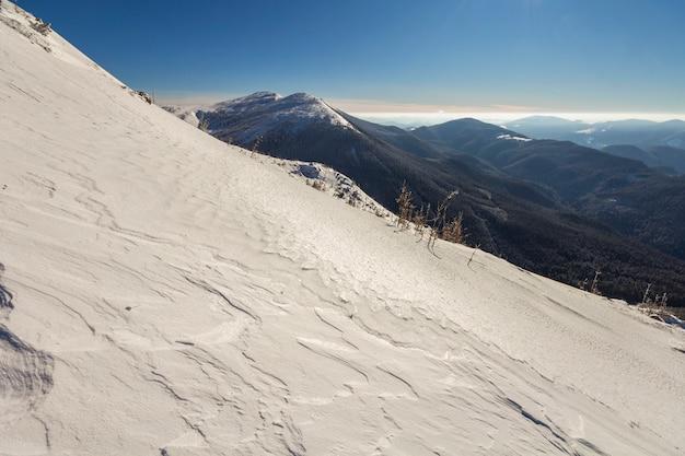 Splendido paesaggio invernale. il pendio ripido della collina della montagna con neve profonda bianca, panorama boscoso distante della catena montuosa che allunga all'orizzonte e raggi luminosi brillanti del sole su cielo blu