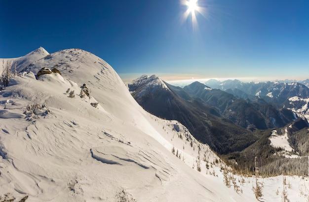 Splendido paesaggio invernale. ripido pendio di montagna con neve profonda bianca, distante catena montuosa boscosa che si estende fino all'orizzonte e raggi di sole splendente sul cielo blu copia spazio