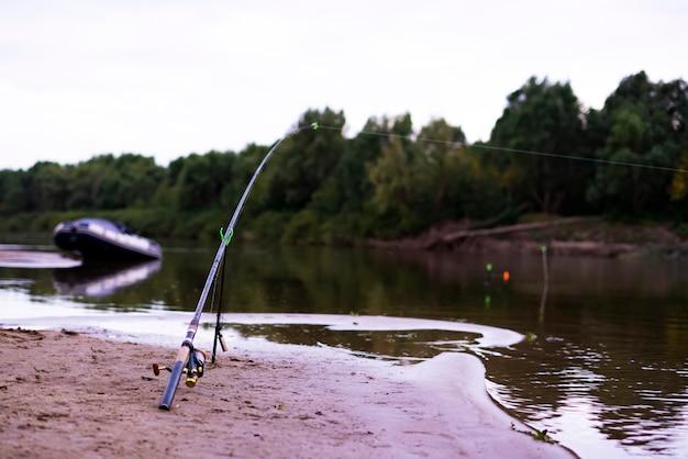 Splendido scenario del concetto di pesca. asta per pesci sulla riva sabbiosa del fiume al crepuscolo d