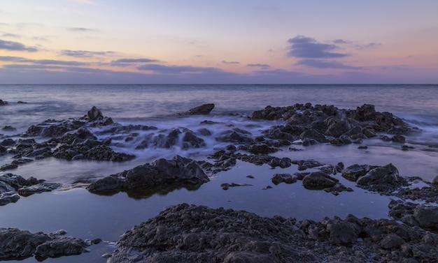 Splendido scenario di enormi formazioni rocciose vicino al mare sotto il cielo al tramonto mozzafiato