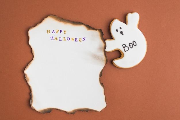 Spook gingerbread vicino al foglio di carta in fiamme