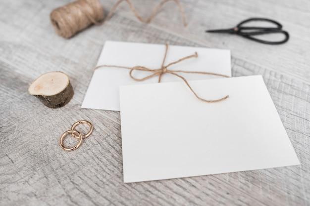 Spool; ceppo di albero in miniatura; fedi nuziali; forbice e busta bianca su fondo di legno