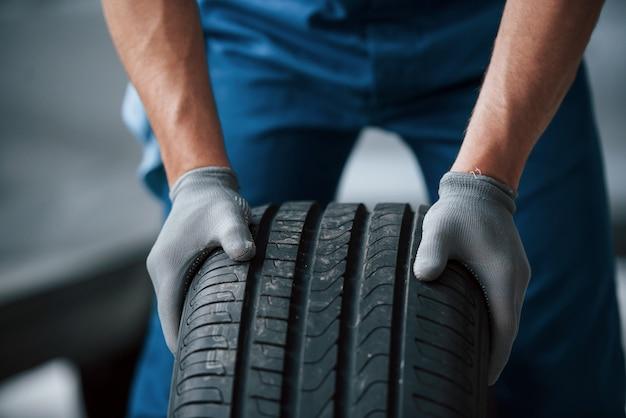 Sporcizia sulla ruota. meccanico che tiene un pneumatico al garage di riparazione. sostituzione di pneumatici invernali ed estivi