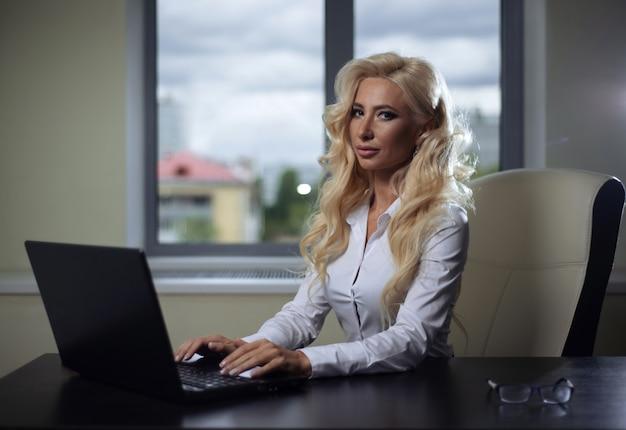 Sporga la ragazza che si siede allo scrittorio in ufficio e che lavora con il computer portatile
