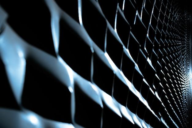 Sporgenze metalliche diagonali illuminate da una luce forte e ombre intense.