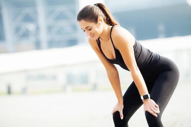 Sport all'aperto, musica d'ascolto della donna sul telefono mentre esercitandosi all'aperto