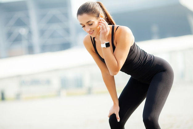 Sport all'aria aperta. musica d'ascolto della donna sul telefono mentre esercitandosi all'aperto