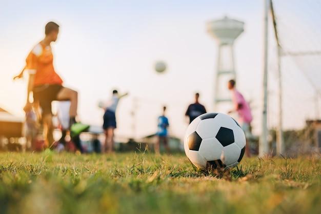 Sport d'azione all'aperto della diversità dei bambini che giocano a calcio calcio per l'esercizio