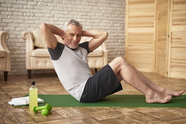 Sport dell'uomo anziano di allenamento a casa di stampa di mattina.