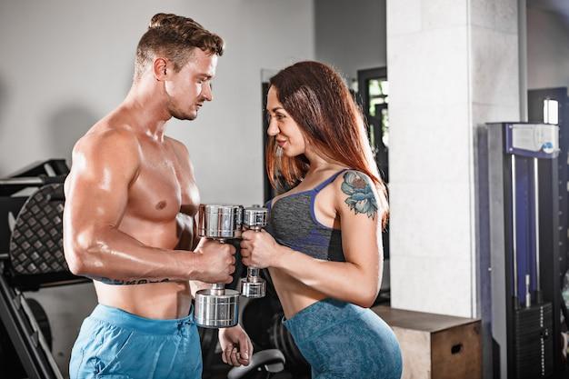 Sport in forma coppia in palestra. lavorare in coppia con manubri