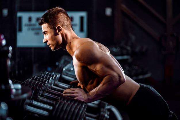 Sport. l'uomo che fa bello spinge aumenta l'esercizio con una mano nella palestra di forma fisica