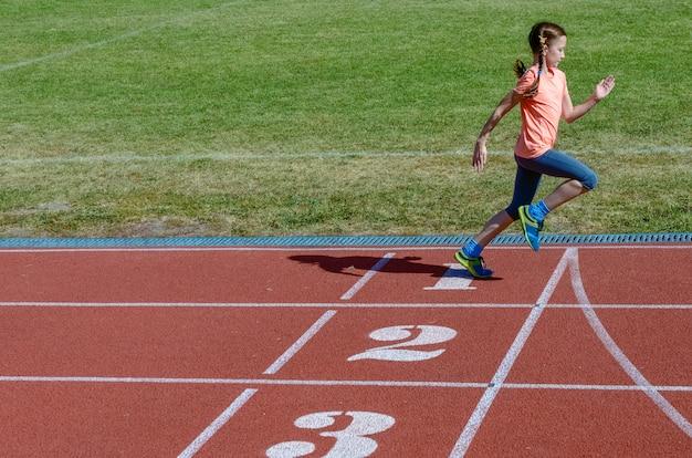 Sport per bambini, bambino che corre sulla pista dello stadio, allenamento e concetto di fitness